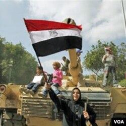 Yon dam egypsyèn ak yon drapo peyi li ka p selebre devan yon tank lame egypsyen an sou plas Tahrir la, nan Lekèr. AP. 02/12/2011