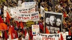 """이스라엘 경제도시 텔아비브에서 물가 상승에 항의하는 시위대가 """"국민은 사회 정의를 요구한다""""는 문구가 적힌 표지판을 들고 시위를 벌이고있다."""