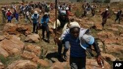 Des mineurs courent en chantant lors d'une grève à la mine Ashanti AngloGold, à Fochville près de Johannesburg, en Afrique du Sud, le 18 octobre 2012. (AP Photo/Themba Hadebe)