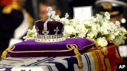 "FILE - The Koh-i-noor, or ""mountain of light,"" diamond, set in the Maltese Cross at the front of the crown made for Britain's late Queen Mother Elizabeth, is seen on her coffin, along with her personal standard, a wreath and a note from her daughter, Quee"