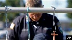 Un aumônier de police se recueille, le 18 juillet 2016, devant un mémorial improvisé sur la scène de fusillade mortelle à Baton Rouge, en Louisiane, où trois agents des forces de loi ont été pris en embuscade et tués par un tireur isolé le dimanche 17 Juillet 2016. (AP Photo/Gerald Herbert)