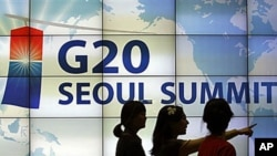 Women walk by a screen showing a G20 Seoul Summit sign at the venue for the upcoming summit meeting, scheduled November 11-12 in Seoul, South Korea, 02 Nov 2010