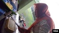 Seorang ibu anggota relawan Omaba sedang menyiapkan nugget tempe untuk makanan balita. (VOA/R. Teja Wulan)