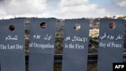 Des militants israéliens et palestiniens brandissent des pancartes en forme de barrière lors d'une marche pour la paix pour protester contre le projet controversé de mur séparant la ville cisjordanienne de Beit Jala et Jérusalem, le 15 janvier 2016.