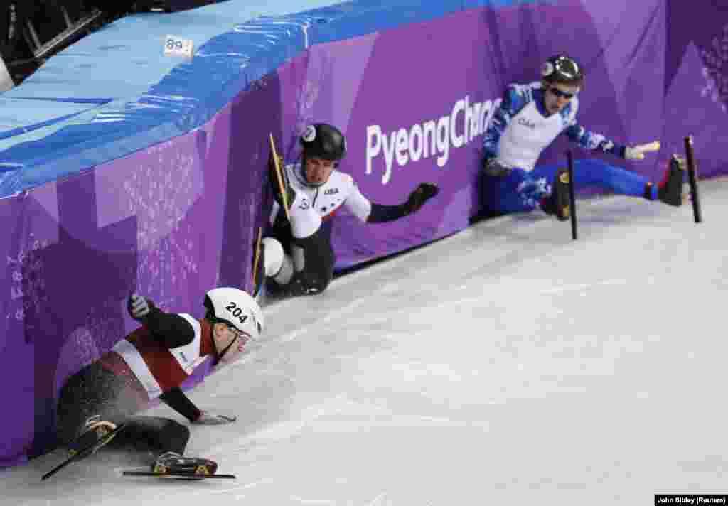 Ковзаняри Роберт Пукітіс з Латвії, J.R. Селский із США та олімпійський атлет з Росії Павло Ситніков впали під час чоловічого змаганя з Швидкісного шорт-треку (1000м - змагання з бігу на ковзанах) 13 лютого, 2018 року.
