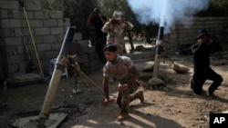 14일 이라크 모술 동부 샤흐라자드 마을에서 정부군이 ISIL 진지를 향해 박격포를 쏘고 있다.