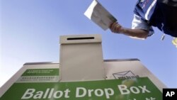 A voter drops off his ballot at a Washington state elections drop box outside of a north Seattle public library, Nov. 6, 2010
