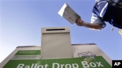A voter drops off his ballot at a King County Elections drop box outside of a north Seattle public library, 02 Nov 2010