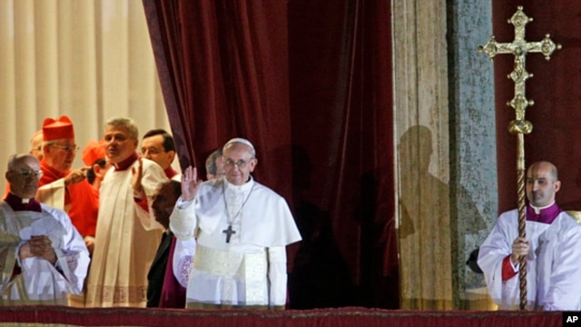 Pope Francis waves to the crowd from the central balcony of St. Peter's Basilica at the Vatican,  March 13, 2013.