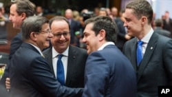 Turkish Prime Minister Ahmet Davutoglu, left, speaks with, from left, French President Francois Hollande, Greek Prime Minister Alexis Tsipras and Estonian Prime Minister Taavi Roivas during a round table meeting at an EU summit in Brussels, March 18, 2016