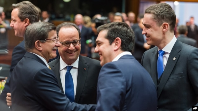 Turkish Prime Minister Ahmet Davutoglu, left, speaks with, from left, French President Francois Hollande, Greek Prime Minister Alexis Tsipras and Estonian Prime Minister Taavi Roivas during a meeting at an EU summit in Brussels, March 18, 2016.