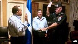 """En esta foto del 22 de may de 2012, el presidente hondureño Porfirio Lobo (izquierda) toma juramento a su nuevo director de policía, Juan Carlos Valladares, también conocido como """"El Tigre"""", señado en violaciones a los derechos humanos la década pasada."""