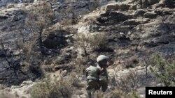 Военные несут остатки ракеты, упавшей наподалеку от деревни Ташкент