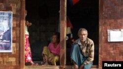 ຊາວເຜົ່າກາຈີ່ນນັ່ງຢູ່ປາກປະຕູສູນອົບພະຍົກຊົ່ວຄາວ ເຂົາເຈົ້າພາກັນ ຫລົບໜີຈາກການຕໍ່ສູ້ລະຫວ່າງ ກອງທະຫານມຽນມາ ແລະກອງທັບເອກກະລາດຂອງເຜົ່າກາຈີ່ນ ຢູ່ນອກເມືອງ Myitkyina ພາກເໜືອຂອງມຽນມາ ທີ່ 22, ກູມພາ 2012.