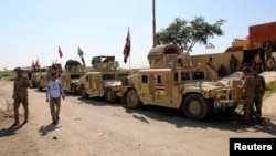 Military vehicles of Iraqi security forces and Shi'ite fighters are seen as they gather at Udhaim dam, north of Baghdad, March 1, 2015.
