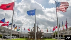 FILE - Flags of member nations flap in the wind outside NATO headquarters in Brussels, Aug. 29, 2014.