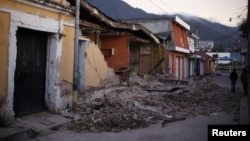 Two men walk past damaged houses after a 7.4-magnitude earthquake struck on the streets of San Marcos, about 250 km south of Guatemala City, November 8, 2012.