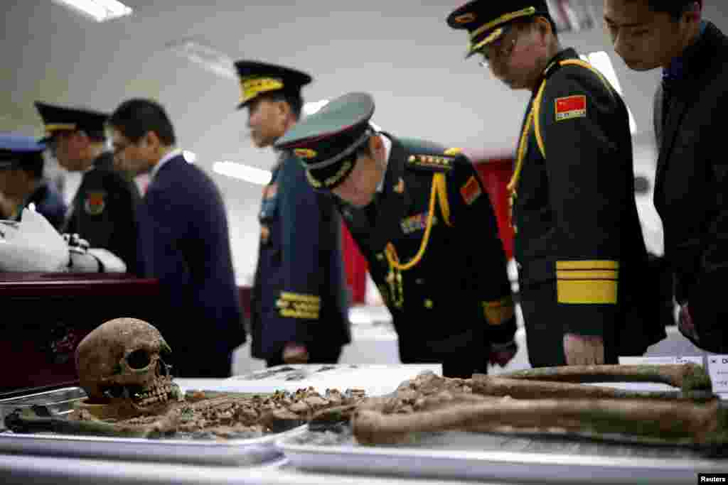 Chinese military officials look at the remains of a Chinese soldier who fought in the Korean War, during the coffin rites in Incheon, South Korea.