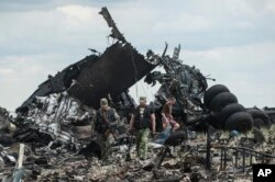 Pro-Russian fighters collect ammunition from the site of remnants of a downed Ukrainian army aircraft Il-76 at the airport near Luhansk, Ukraine, June 14, 2014.