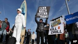 Scott Thompson, left, leans against his surfboard as he joins a gathering at a rally in Asbury Park, N.Y., to oppose federal plans that would allow oil and gas drilling in the Atlantic Ocean, Jan. 31, 2016. President Barack Obama has now designated the bu