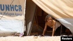 Seorang anak perempuan mengamati dari tenda penampungannya di Al Zaatri dekat kota Mafraq, Jordania dekat perbatasan dengan Suriah (Foto: dok).