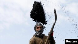 FILE - A laborer unloads coal from a truck at a coal dump site on the outskirts of Kabul, Afghanistan March 7, 2017.