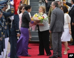 Chile's President Michelle Bachelet, center right, receives flowers as she arrives at Manila's international airport, Philippines, to attend the Asia Pacific Economic Cooperation (APEC) summit, Nov. 15, 2015.