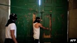 27일 복면을 두른 팔레스타인 인들이 이스라엘 경찰과의 충돌에 대비해 알아크사 사원 정문을 걸어 잠그고 있다.