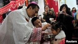 沈阳一位天主教教士在复活节弥撒中给小女孩施洗礼