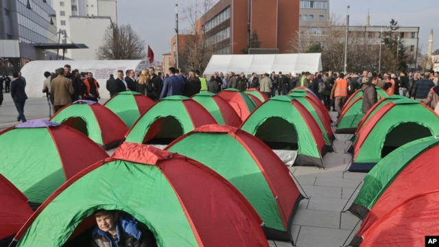 A child plays inside a tent set up by Kosovo opposition supporters in front of the main governing building in Kosovo's capital Pristina, Feb. 23, 2016.