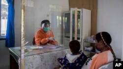 Seorang tenaga kesehatan berbicara dengan seorang pasien dari balik pelindung plastik untuk mencegah penularan virus corona di sebuah puskesmas di Yalimo, Provinsi Papua, 21 April 2020. (Foto: AP)