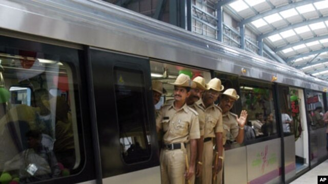 Indian policemen take a ride during the inaugural run of the Bangalore Metro rail in Bangalore, India, October 20, 2011.