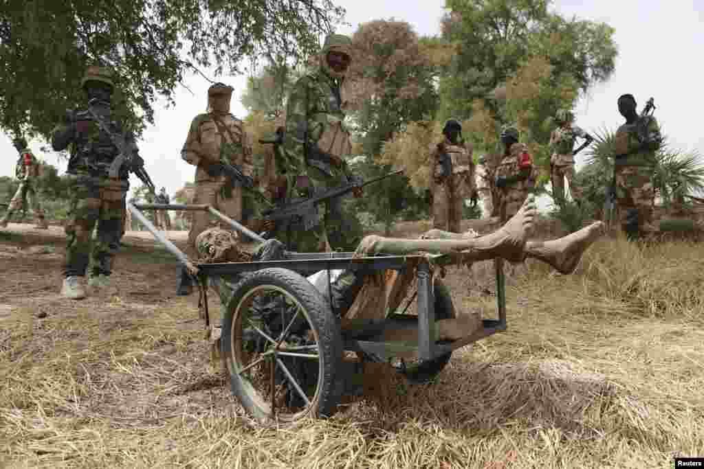 Des soldats transportent un cadavre en décomposition qu'ils ont trouvé dans une fosse commune dans la ville de Damasak récemment reprise de mains de Boko Haram, le Nigeria, vendredi 20 mars 2015.