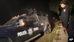 Police agent stands guard as Mexican Federal Police vehicle leaves village of Hueypoxtla, Dec. 4, 2013.