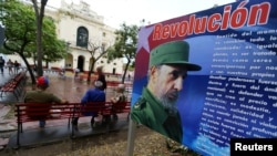 FILE - People sit in front of a billboard with a message about Cuba's late President Fidel Castro in Santa Clara, Cuba, Nov. 30, 2016.