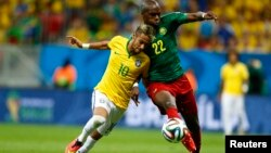 Neymar (gauche) se bat pour le ballon avec Allan Nyom du Cameroun lors de la Coupe du Monde 2014 dans le groupe A au stade national à Brasilia, 23 juin, 2014. REUTERS / Dominic Ebenbichler