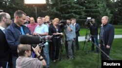 Russia's President Vladimir Putin (R) talks to journalists in the far eastern city of Vladivostok, Aug. 31, 2013.