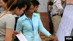 Cambodian Election workers check the voter rolls at a polling station in Kampong Cham, northeast of Phnom Penh, July 28, 2013. (Heng Reaksmey/VOA Khmer)