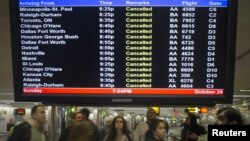 在紐約拉瓜迪亞機場的旅客星期天注視顯示航班取消