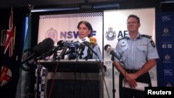 FILE - Australian Federal Police Deputy Commissioner Michael Phelan (R) listens as New South Wales Deputy Police Commissioner Catherine Burn speaks during a media conference in Sydney, Feb. 11, 2015.