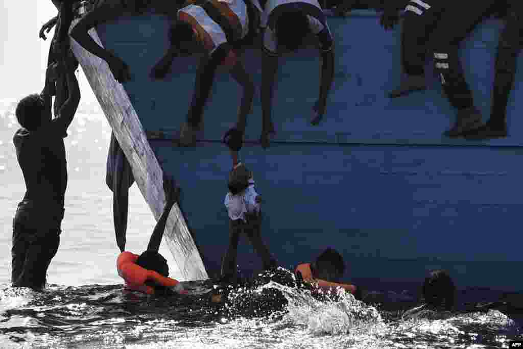 Migrants try to pull a child out of the water as they wait to be rescued by members of Proactiva Open Arms NGO in the Mediterranean Sea, some 12 nautical miles north of Libya, Oct. 4, 2016.