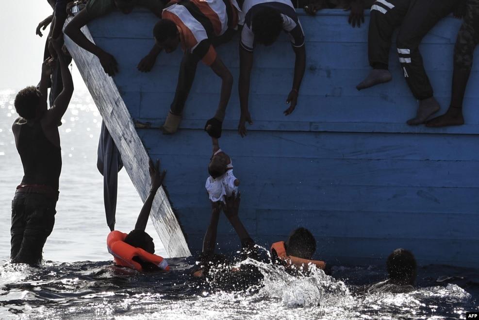지난 4일(현지시간) 지중해 리비아 북쪽 연안에서 스페인 구호단체 '프로악티바 오픈암스(Proactiva Open Arms)'에 구출되고 있는 난민들이 어린이를 배 위로 끌어올리고 있다.