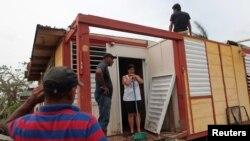 Des familles nettoient ce qui reste de leurs maisons après le passage de l'ouragan Maria à Toa Baja, Porto Rico, 18 octobre 2017.