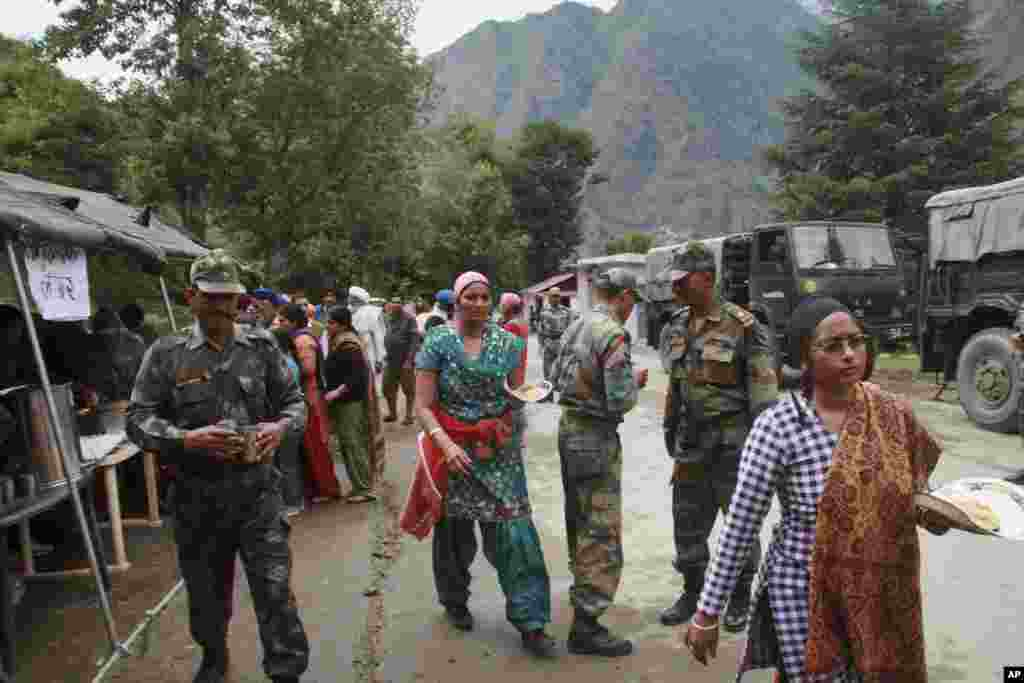 Indian army personnel distribute free food to stranded pilgrims after they were rescued from one of the worst flood affected region in Govind Ghat, in the northern Indian state of Uttarakhand, India, June 18, 2013.