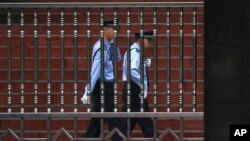 FILE - Chinese policemen are seen on patrol in southwest China's Sichuan province, Sept. 24, 2012. A police report on the death of a 14-year-old student whose body was found outside his dormitory at Taifu Middle School in Luzhou, Sichuan province, has raised questions about the investigation.