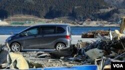 Sebuah mobil lewat di depan tumpukan puing-puing (15/1) akibat bencana tsunami di dermaga di Ofunato, Iwate, hampir satu tahun setelah tsunami menghancurkan daerah tersebut pada 11 Maret 2011 (AFP).