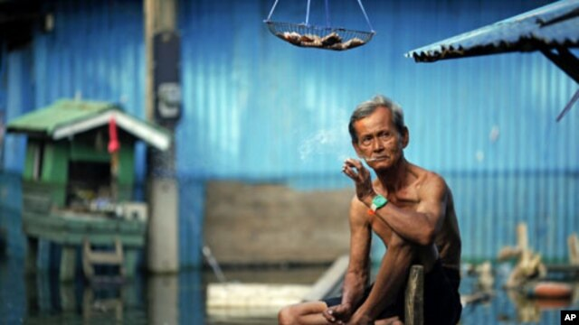 A man smokes a cigarette outside his flooded home in a slum just outside Bangkok, Thailand, November 21, 2011.