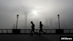 FILE - People jog past the Pudong Financial District shrouded in fog and pollution at the Shanghai Bund in Shanghai, China, Thursday, April 14, 2016. Air pollution has caused 5.5 million premature deaths globally in 2013, outpacing disease, a new study has found.