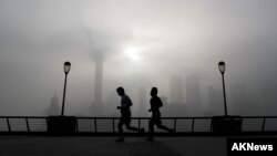 FILE - People jog past the Pudong Financial District shrouded with fog and pollution at the Shanghai Bund in Shanghai, China, April 14, 2016.