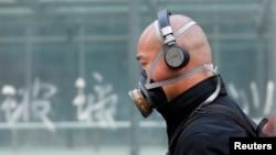 Seorang pria China harus mengenakan masker akibat udara kotor dan kabut asap yang menyelimuti Beijing (foto: dok).